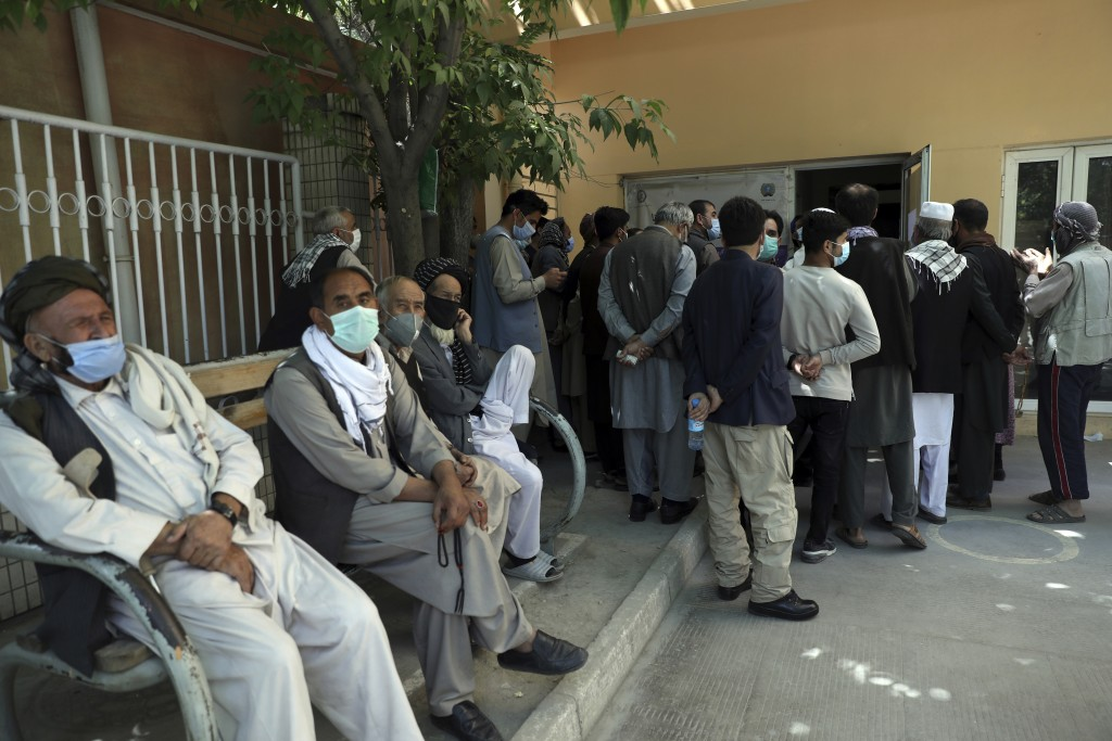 Residents wearing face masks to help curb the spread of the coronavirus line up to receive the Sinopharm COVID-19 vaccine at a vaccination center in K...
