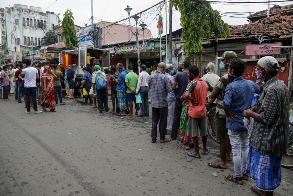 People line up to receive free meal distributed by a voluntary organization during relaxation hours of a lockdown put in place to curb the spread of c...