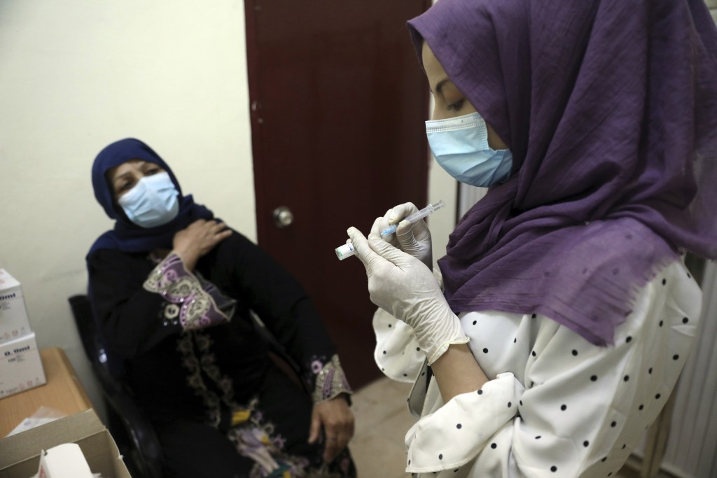 A doctor fills a syringe with the Sinopharm COVID-19 vaccine at a vaccination center in Kabul, Afghanistan, Wednesday, June 16, 2021. (AP Photo/Rahmat...