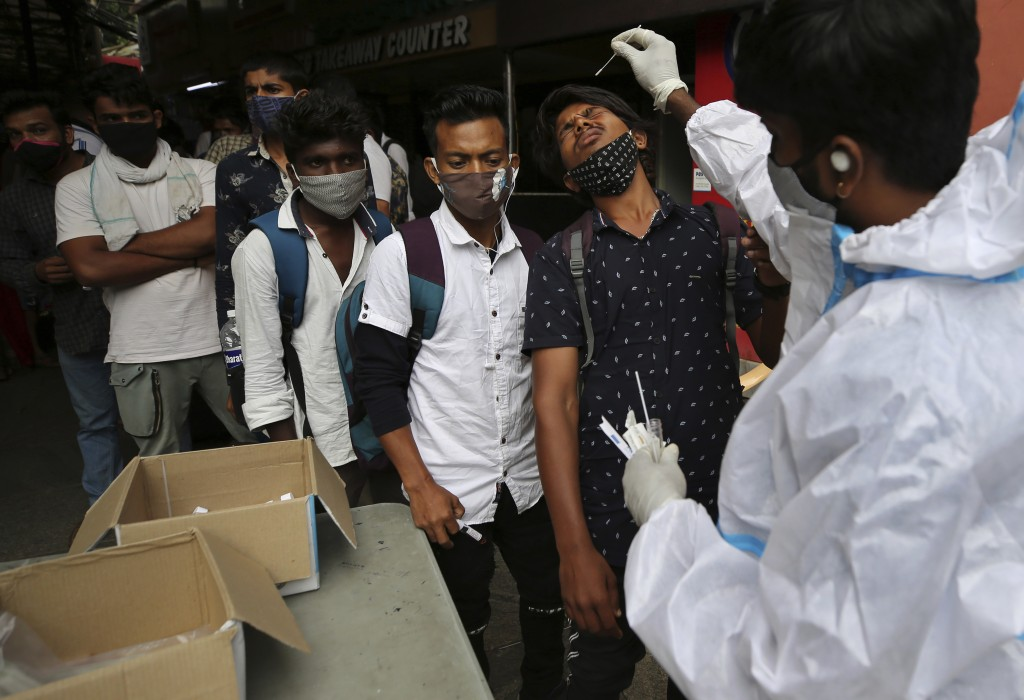 A health worker in protective suit collects nasal swab sample of a traveler to test for COVID-19 outside a train station in Bengaluru, India, Wednesda...