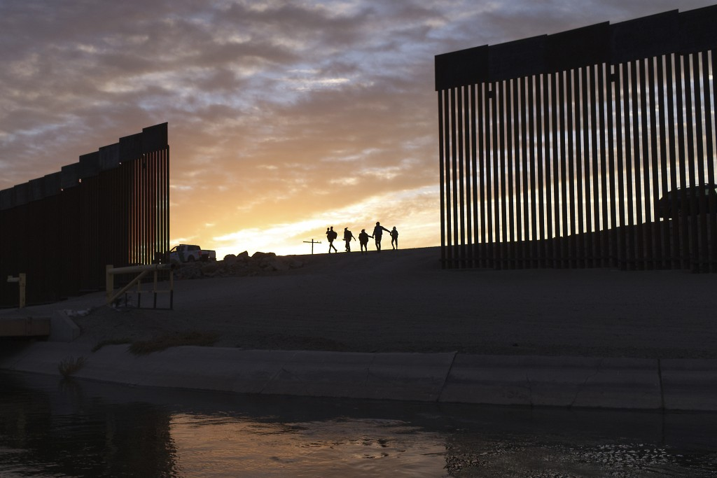 FILE - In this Thursday, June 10, 2021, file photo, a pair of migrant families from Brazil pass through a gap in the border wall to reach the United S...