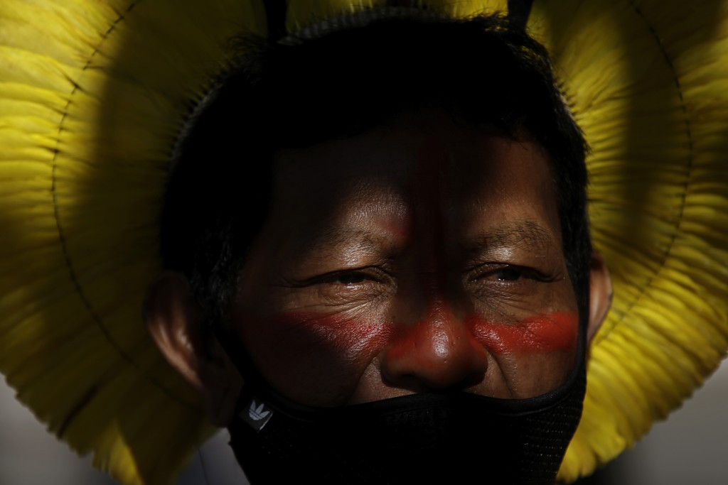 An Indigenous man wearing a mask amid the COVID-19 pandemic takes part in a protest against Brazilian President Jair Bolsonaro's proposals to allow mi...