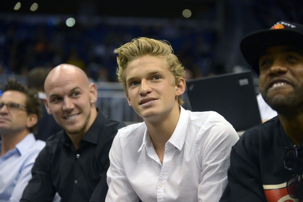 Singer Cody Simpson, second from right, watches an Orlando Magic game from his court-side seats during the first half of an NBA basketball game agains...