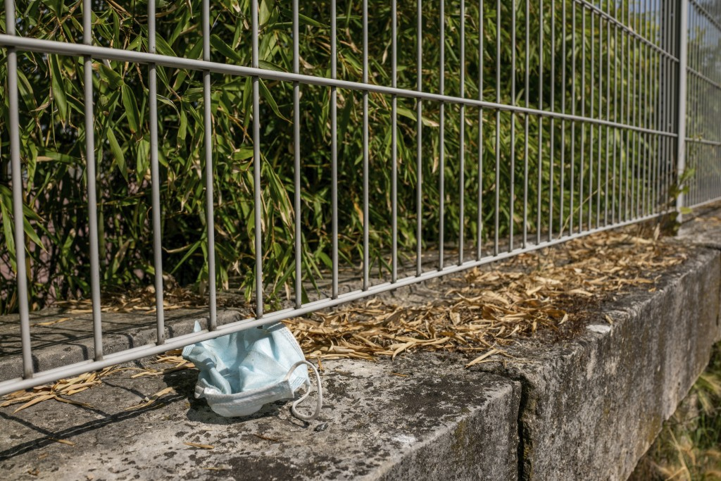 An abandoned mask is pictured in a garden Wednesday, June 16, 2021 in Paris. France on Wednesday eased several COVID-19 restrictions, with authorities...