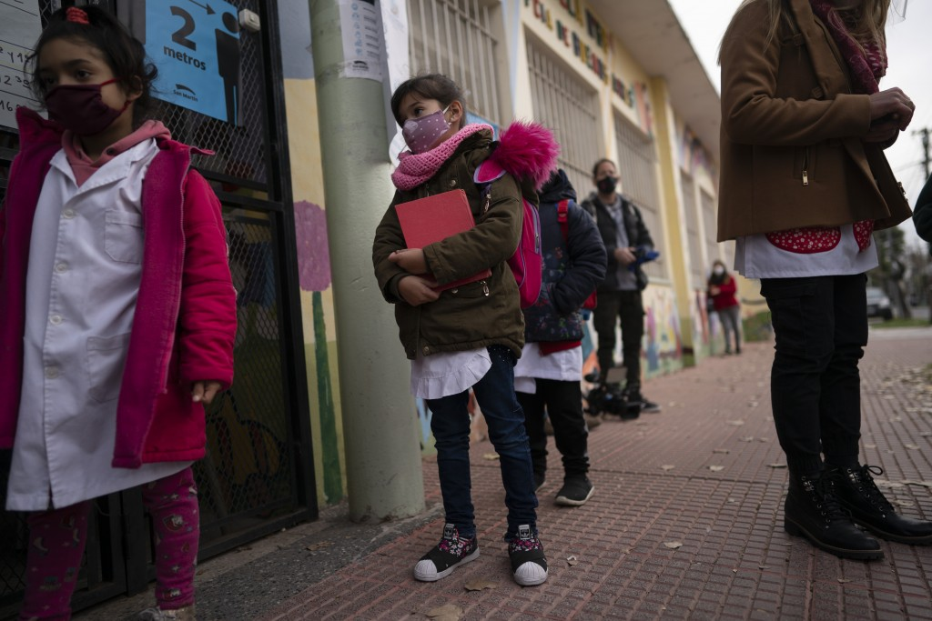 Children stand in line to enter their elementary school in San Martin, a municipality in the Buenos Aires province, Argentina, Wednesday, June 16, 202...