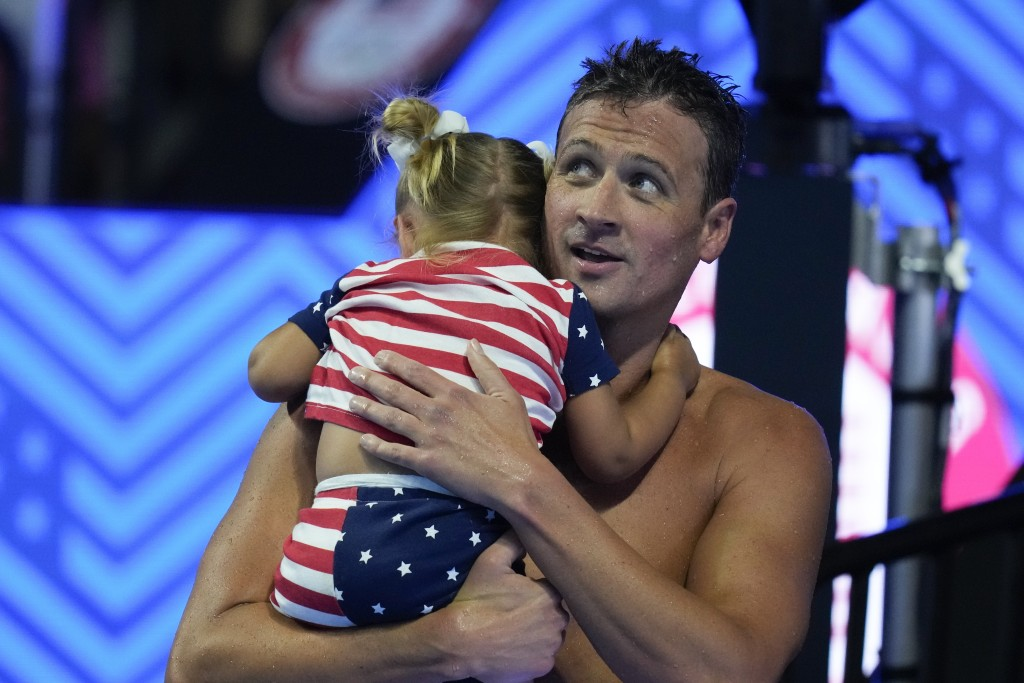 Ryan Lochte holds his daughter after his heat in the men's 200 Individual Medley during wave 2 of the U.S. Olympic Swim Trials on Thursday, June 17, 2...