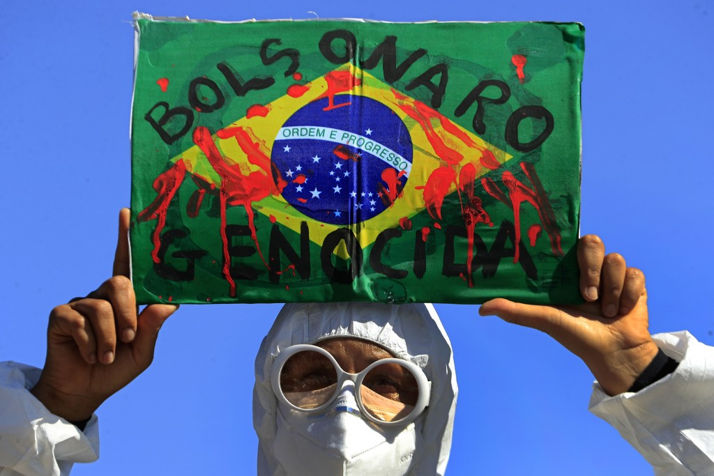 """FILE - In this May 26, 2021 file photo, a demonstrator holds an image of the Brazilian flag covered in fake blood and the Portuguese phrase """"Bolsonaro..."""