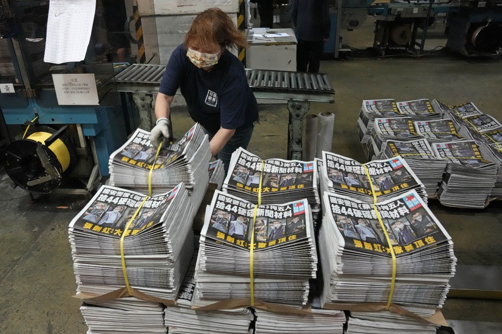 A worker packs copies of Apple Daily newspaper at the printing house in Hong Kong, early Friday, June 18, 2021. Five editors and executives at pro-dem...