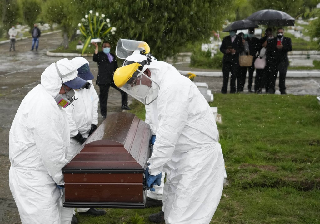 Cemetery and funeral workers carry the coffin containing the remains of a man who died of COVID-19 at the Zipaquira's Park Cemetery in Zipaquira, Colo...