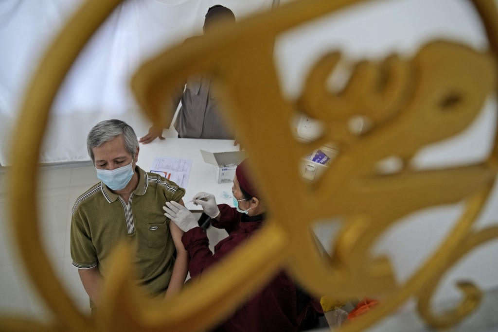 """A man is seen through a mosque ornament in Arabic writing that reads: """"Muhammad"""" as he receives a shot of the AstraZeneca vaccine for COVID-19 during ..."""