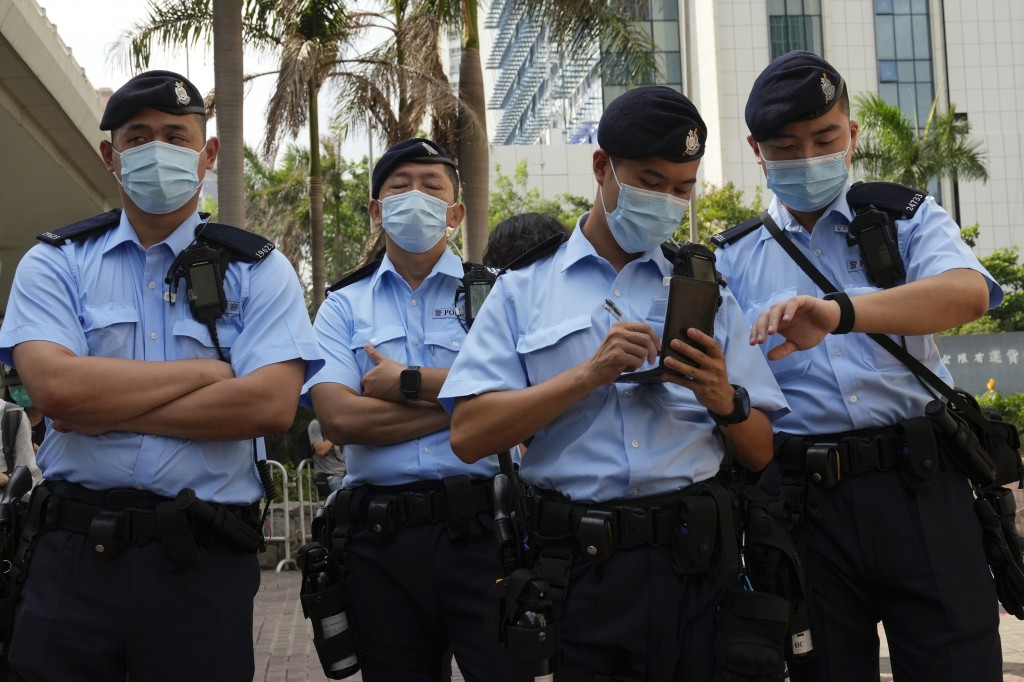 Police officers stand guard outside a court in Hong Kong, Saturday, June 19, 2021. The top editor of the Hong Kong's pro-democracy newspaper and the h...