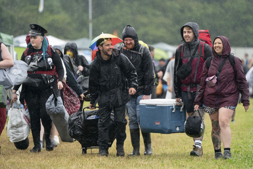 Festivalgoers arrive during a downpour on the first day of Download Festival at Donington Park at Castle Donington, England, Friday June 18, 2021. The...