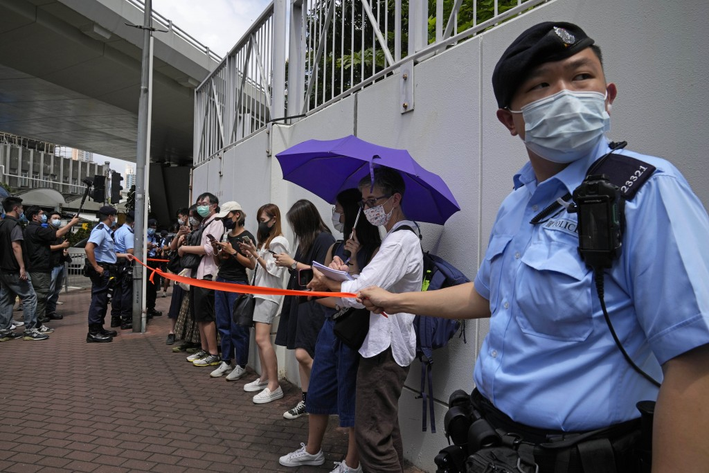 Police get people, including journalists, together to check IDs outside a court in Hong Kong, Saturday, June 19, 2021. A Hong Kong court ordered the t...