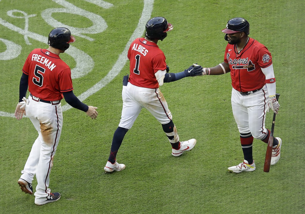 Atlanta Braves' Ozzie Albies (1) is congratulated by Abraham Almonte, right, after hitting a two-run home run off St. Louis Cardinals pitcher Carlos M...
