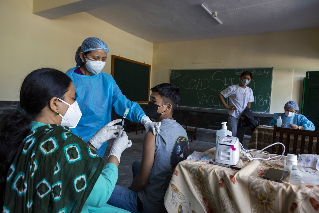 An exile Tibetan nurse in protective suit prepares another Tibetan to receive a Covishield -19 vaccine in Dharmsala, India, Saturday, June 19, 2021. (...