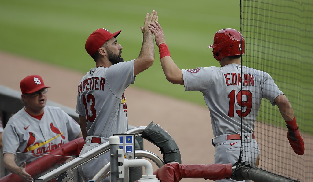 St. Louis Cardinals' Tommy Edman (19) is congratulated by Matt Carpenter (13) after scoring against the Atlanta Braves during the first inning of a ba...
