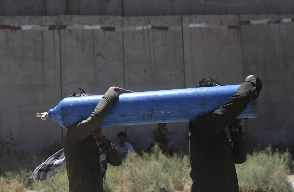 Men carry a cylinder to be refilled from a privately owned oxygen factory, in Kabul, Afghanistan, Saturday, June 19, 2021. Health officials say Afghan...