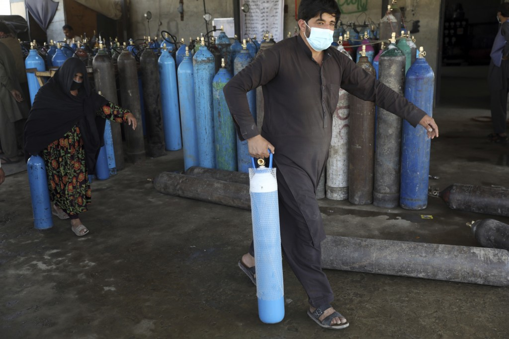 A man and woman carry an oxygen cylinders from a privately owned oxygen factory, in Kabul, Afghanistan, Saturday, June 19, 2021. Health officials say ...