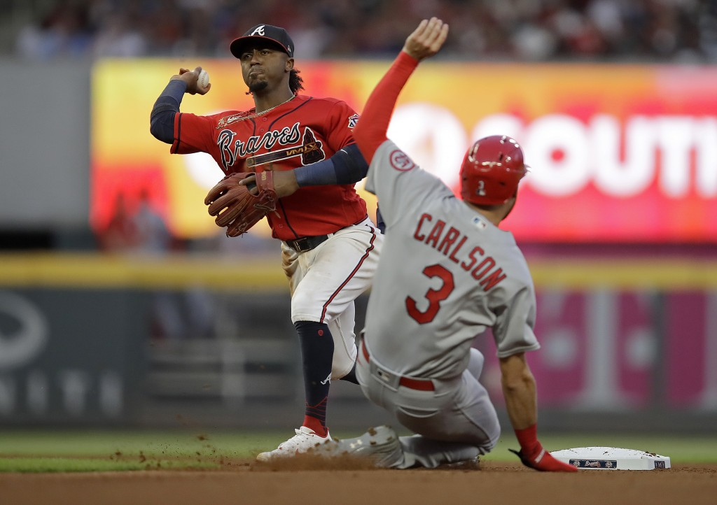 Atlanta Braves' Ozzie Albies, left, prepares his throw to first base to complete a double play after making the out on St. Louis Cardinals' Dylan Carl...