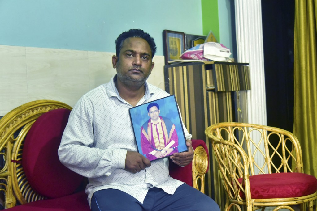 A relative holds a photograph of Dr. Jibraeil, assistant professor of history at Aligarh Muslim Uliversity, who died of COVID-19, in Aligarh, India, S...