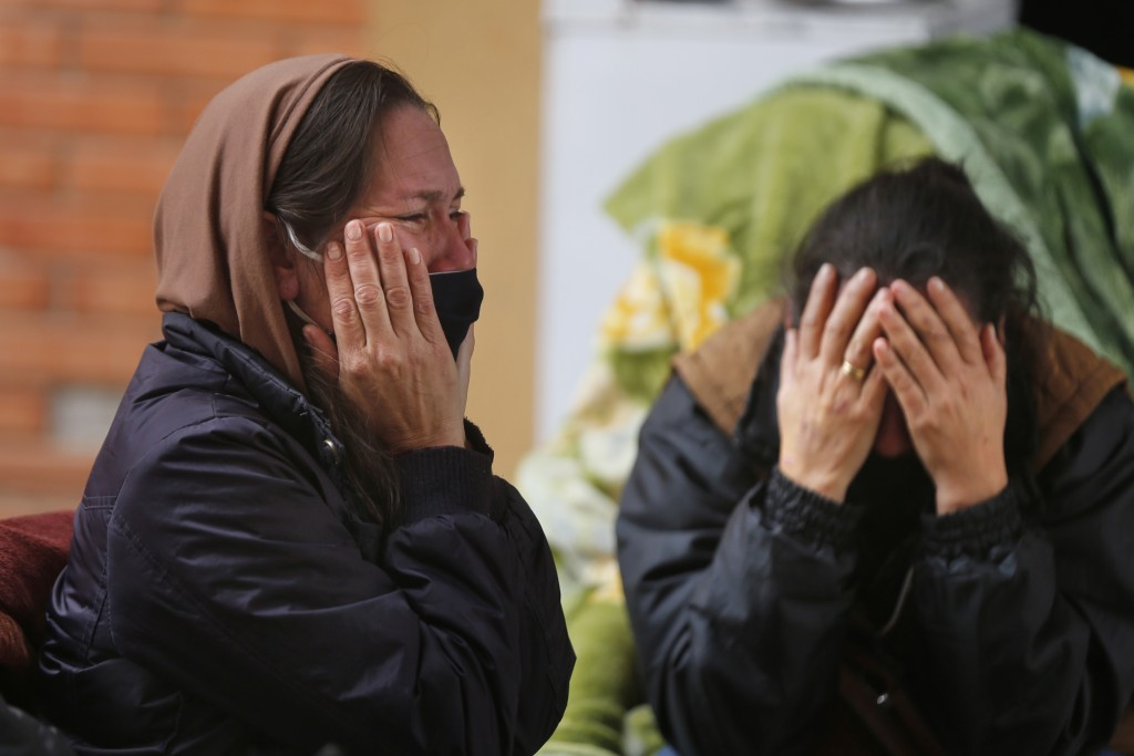The daughters of Isidra Coronel cry after learning their mother died from the new coronavirus, at Hospital de Clinicas in San Lorenzo, Paraguay, Frida...