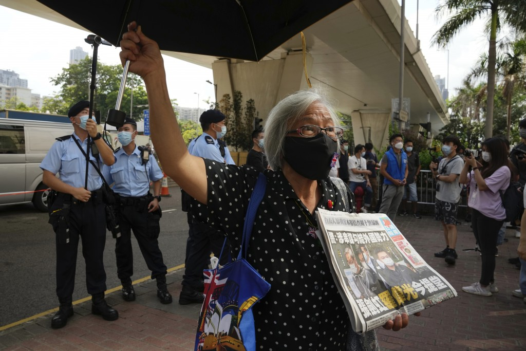 A pro-democracy activist holding a copy of Apple Daily newspaper protests outside a court in Hong Kong, Saturday, June 19, 2021, to demand to release ...