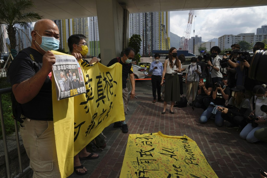 Pro-democracy activists holding a copy of Apple Daily newspaper and banner protest outside a court in Hong Kong, Saturday, June 19, 2021, to demand to...