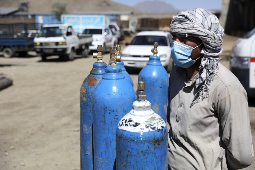 A man waits inside a privately owned oxygen factory to get his oxygen cylinders refilled, in Kabul, Afghanistan, Saturday, June 19, 2021. Health offic...