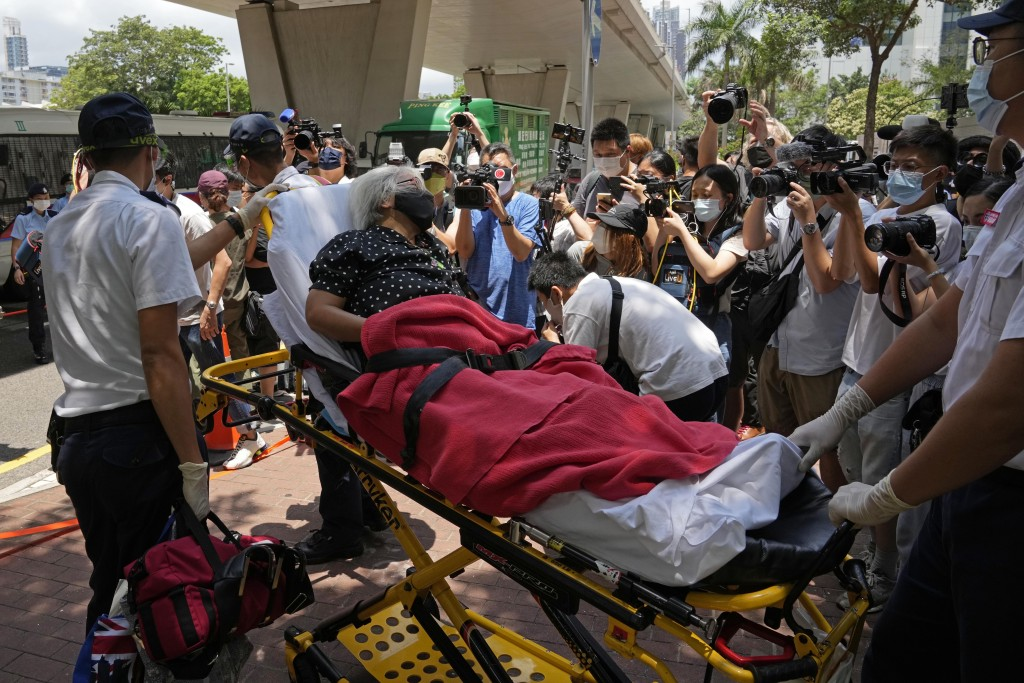 A pro-democracy protester is sent to a hospital as she feels sick outside a court in Hong Kong, Saturday, June 19, 2021.  Hong Kong court ordered the ...