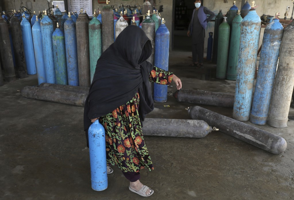 A woman carries an oxygen cylinder from a privately owned oxygen factory, in Kabul, Afghanistan, Saturday, June 19, 2021. Health officials say Afghani...
