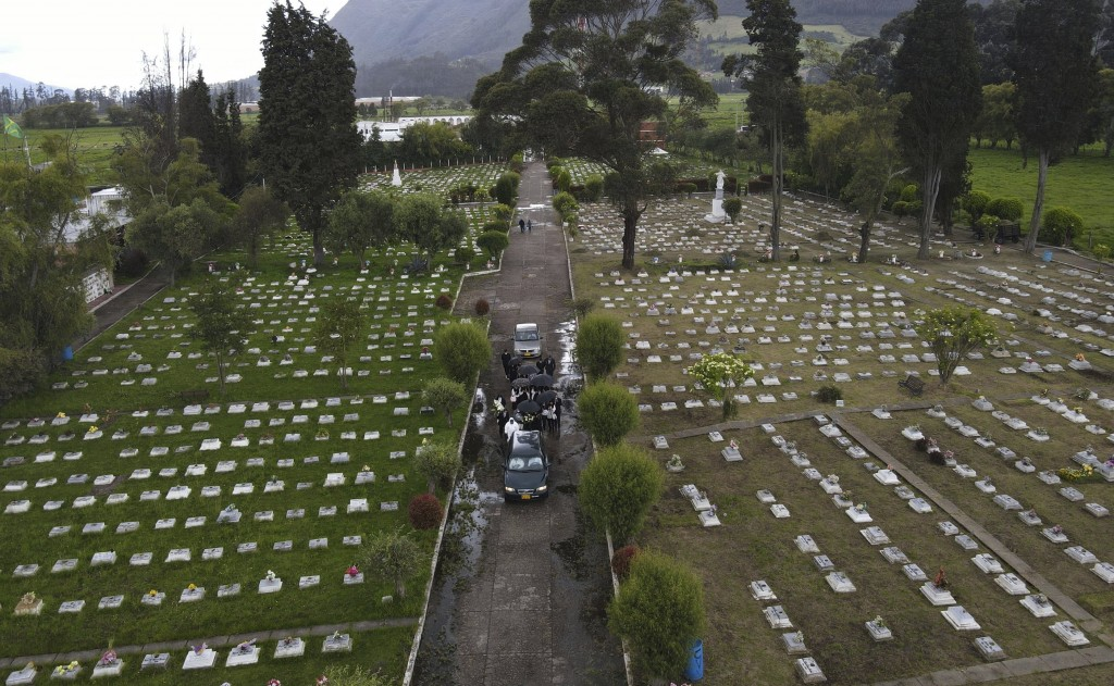 Family and friends follow a hearse transporting the coffin containing the remains of a relative who died from the new coronavirus, at the Zipaquira's ...