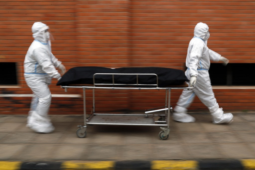 Nurses take the body of Isidra Coronel to the morgue after removing her body from a hospital bed where she died from the new coronavirus at Hospital d...