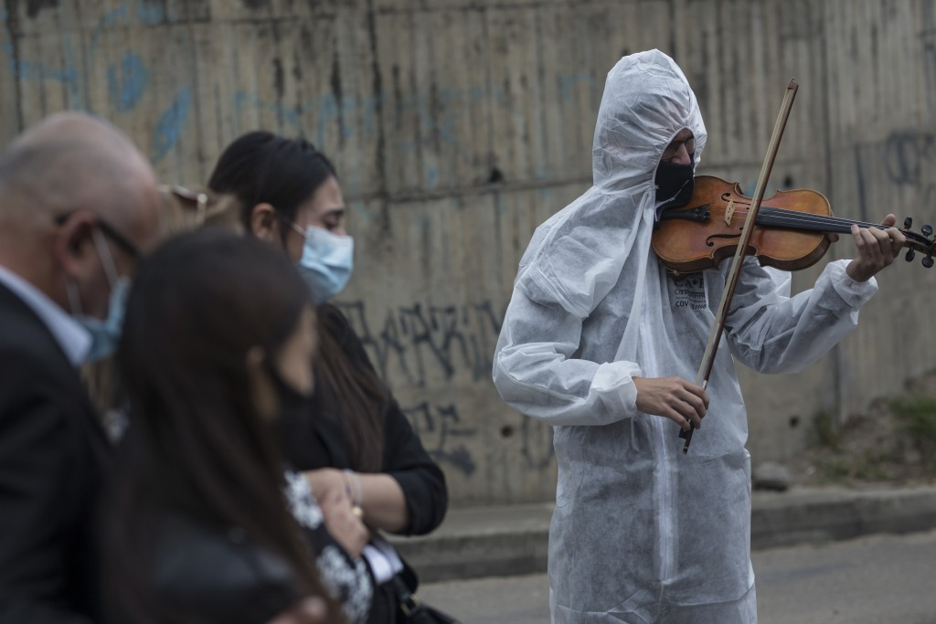 Violinist Antonio Hernandez plays for the relatives of COVID-19 victim Miryam Rodriguez, while they are gathered for prayer by the hearse that carries...