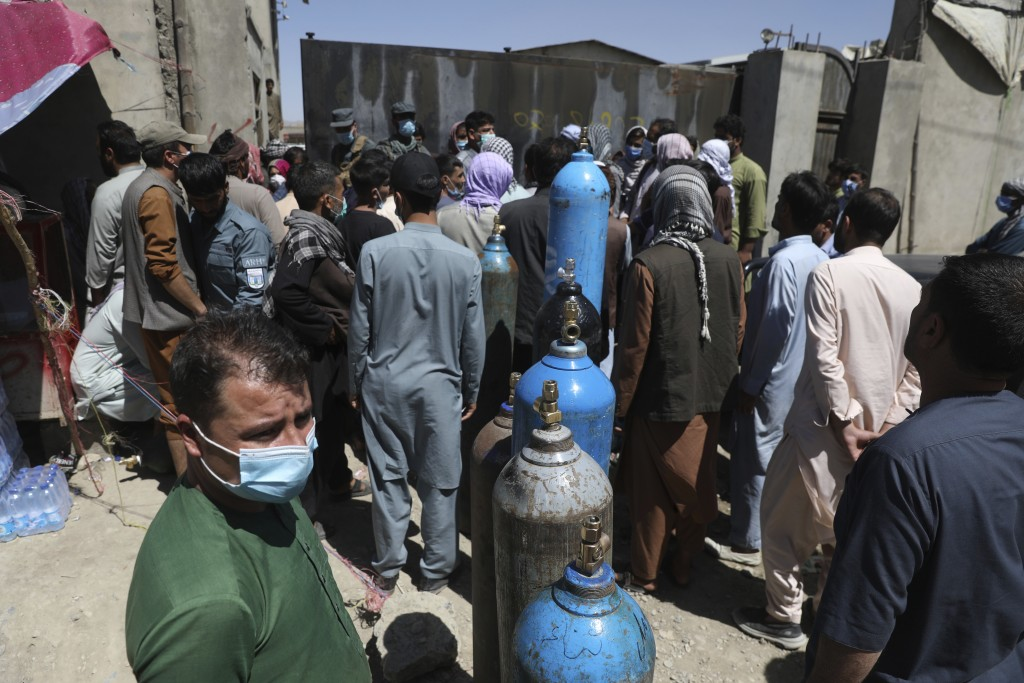 Men wait outside a privately owned oxygen factory to get their oxygen cylinders refilled, in Kabul, Afghanistan, Saturday, June 19, 2021. Health offic...