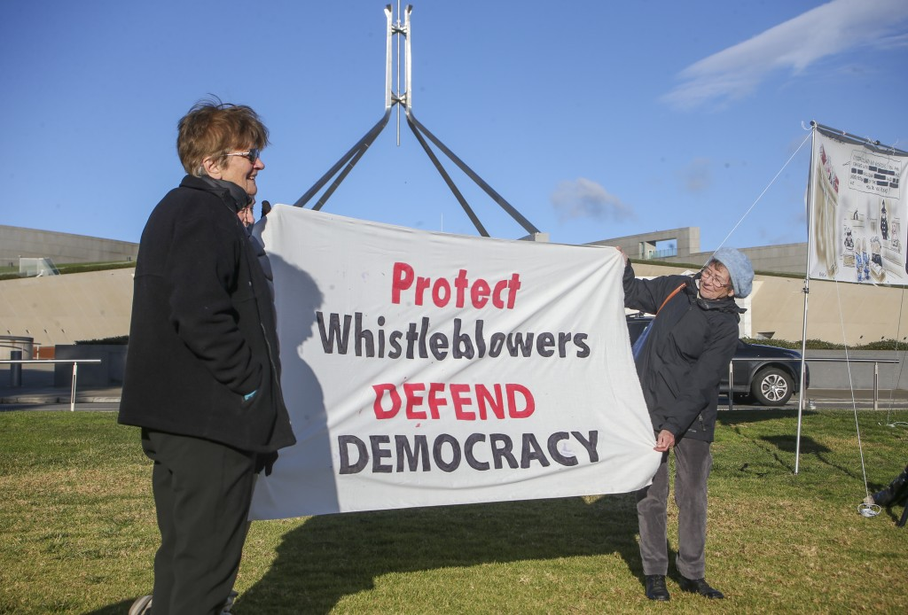 Demonstrators hold a banner during a protest outside Parliament House in Canberra, Australia, Thursday, June 17, 2021 against the prosecution of lawye...