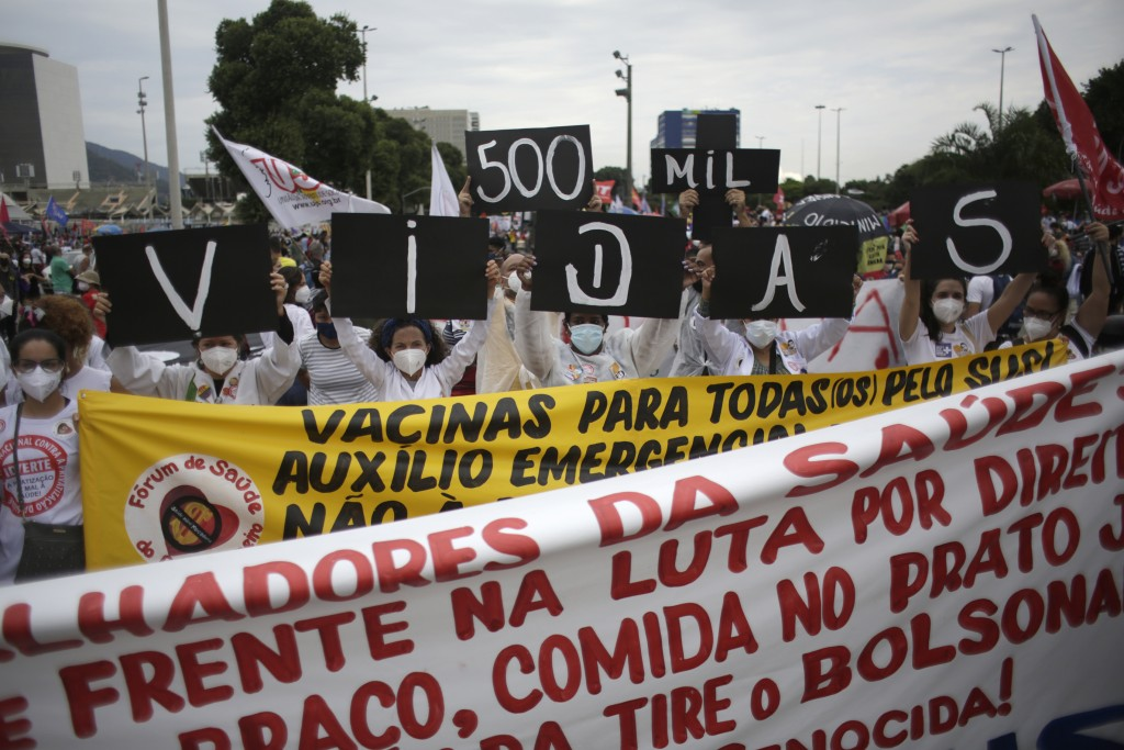"""Women simultaneously hold up placards with a message that reads in Portuguese; """"500K deaths! His fault!"""" during a demonstration against Brazilian Pres..."""