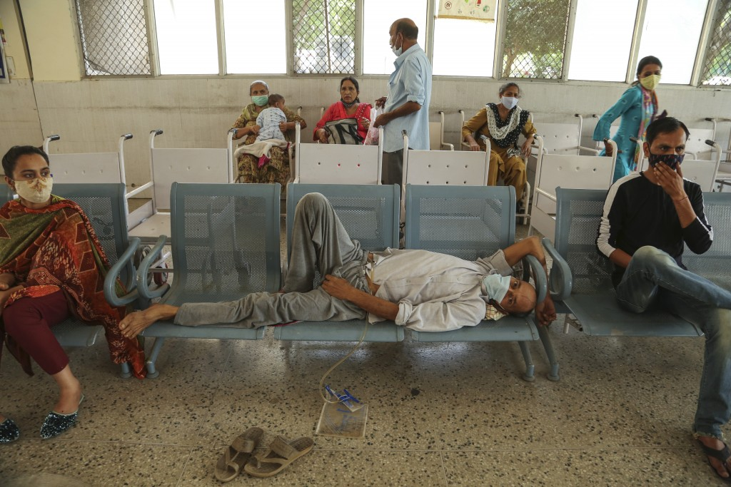 People wearing face masks as a precaution against the coronavirus wait for doctor consultation at a government hospital in Jammu, India, Monday, June ...
