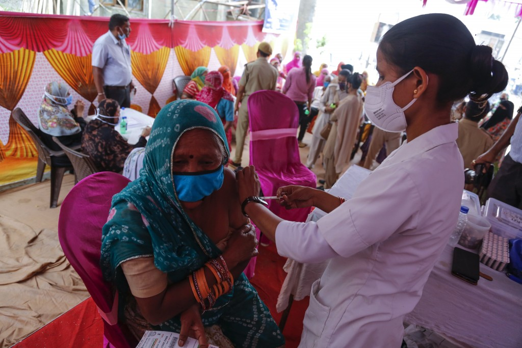 A woman is administered the Covishield vaccine during a vaccination drive against COVID-19 at a mosque in Ahmedabad, India, Monday, June 21, 2021. Eve...