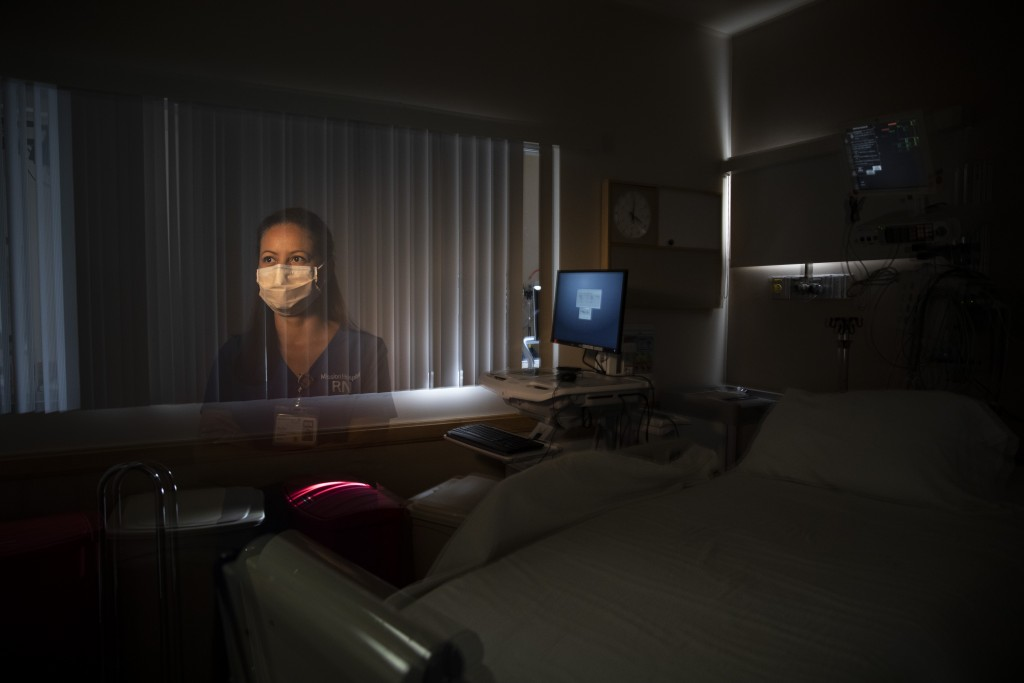 In this photo created with an in-camera multiple exposure, registered nurse Elisa Castorena, part of a group of nurses who had been treating coronavir...