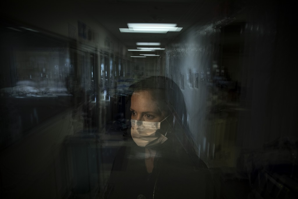 In this photo created with an in-camera multiple exposure, registered nurse Lisa Lampkin, part of a group of nurses who had been treating coronavirus ...