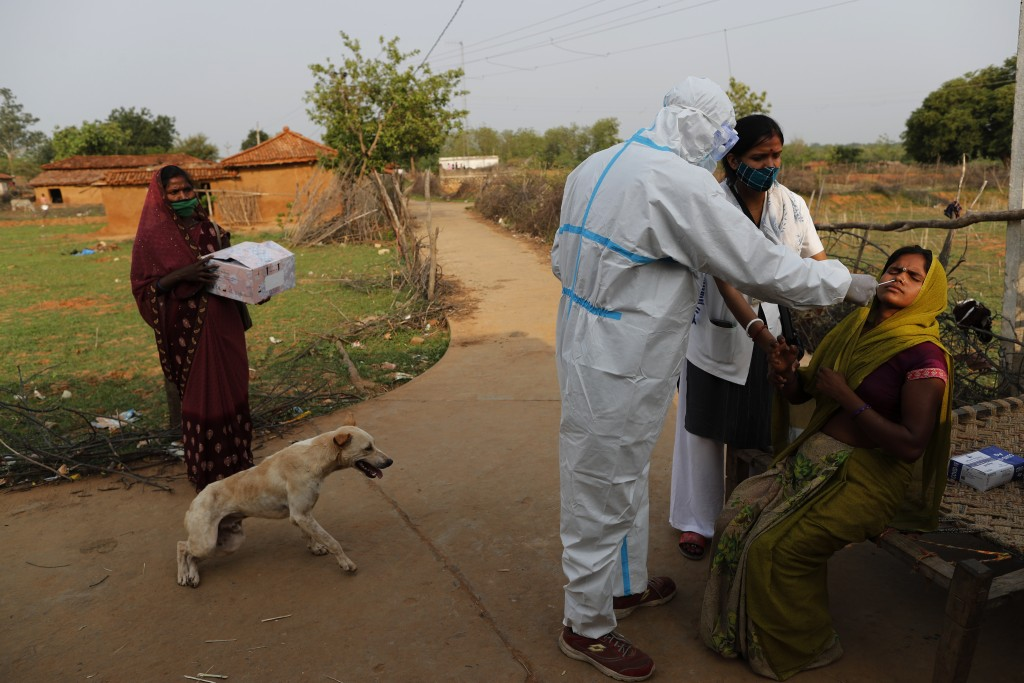 Health workers Neeraj, third right, and Aradhna take nasal sample of a woman for COVID-19 test at Jamsoti Village, in Chandauli district, Uttar Prades...