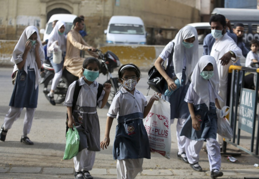 Student wearing face masks to help prevent the spread of the coronavirus arrive at a school in Karachi, Pakistan, Monday, June 21, 2021. Authorities o...