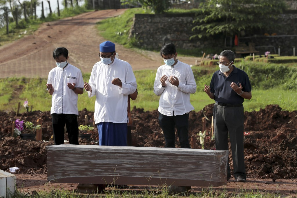 An Islamic cleric leads relatives in prayer during the burial of a man in the special section of Jombang Public Cemetery reserved for those who died o...