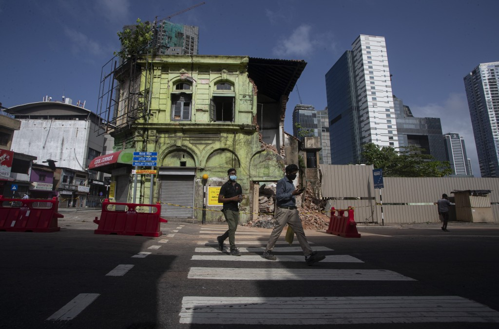 People cross a road as they return to work in the morning in Colombo, Sri Lanka, Monday, June 21, 2021. Sri Lanka eased a nearly one month-long travel...