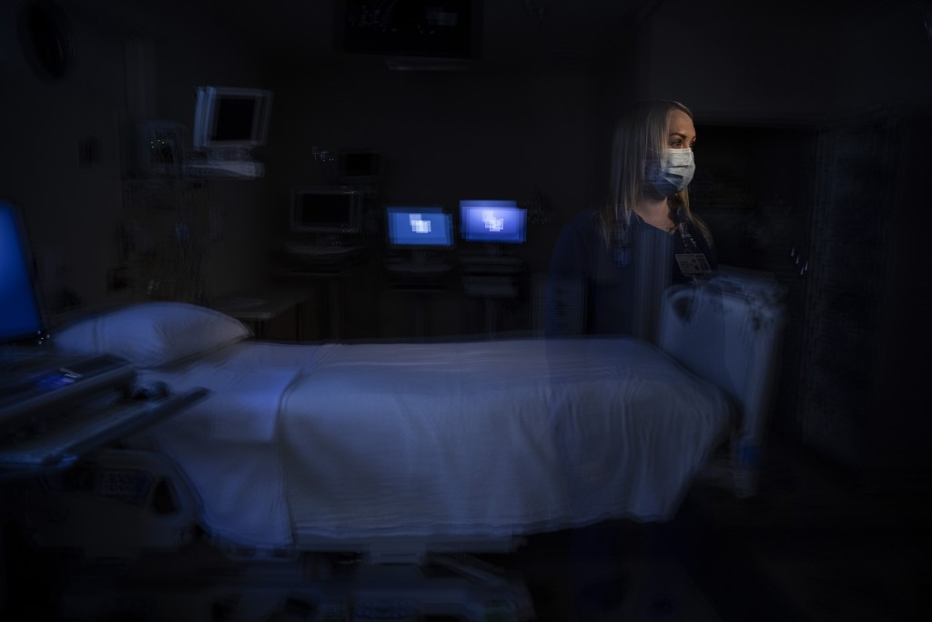In this photo created with an in-camera multiple exposure, registered nurse Jamie Corcoran, part of a group of nurses who had been treating coronaviru...