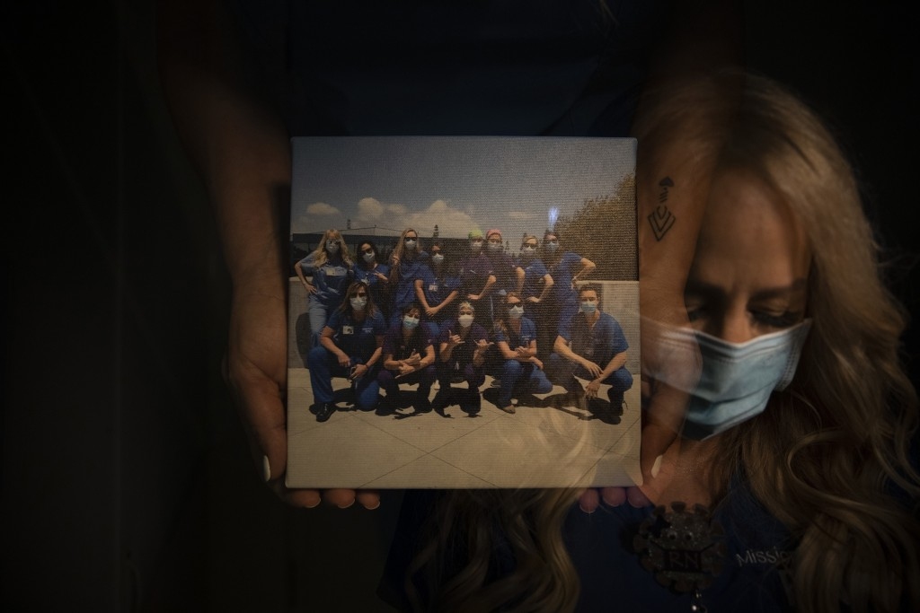 In this photo created with an in-camera multiple exposure, registered nurse Debbie Wooters, part of a group of nurses who had been treating coronaviru...