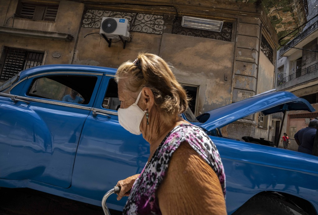 A woman, wearing a protective face mask as a precaution against the spread of the new coronavirus, walks past in Havana, Cuba, Wednesday, June 2, 2021...