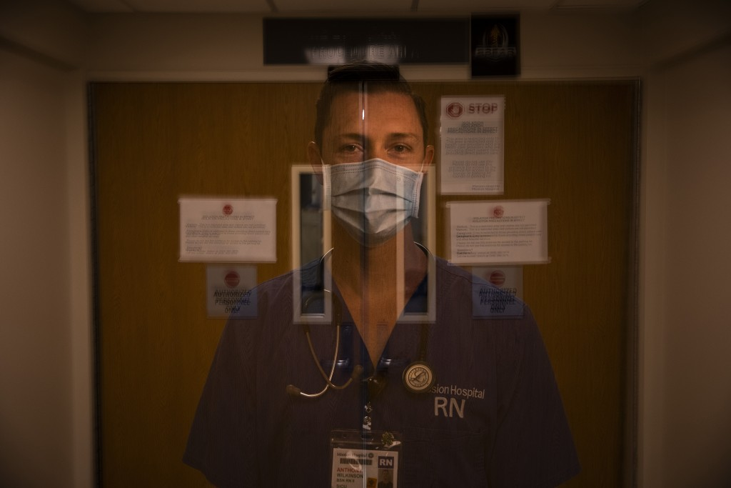 In this photo created with an in-camera multiple exposure, registered nurse Anthony Wilkinson, part of a group of nurses who had been treating coronav...