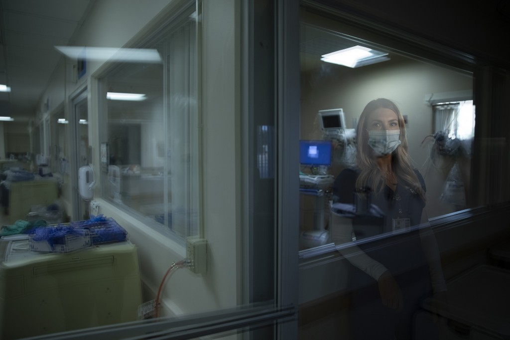 In this photo created with an in-camera multiple exposure, registered nurse Jill Shwam, part of a group of nurses who had been treating coronavirus pa...