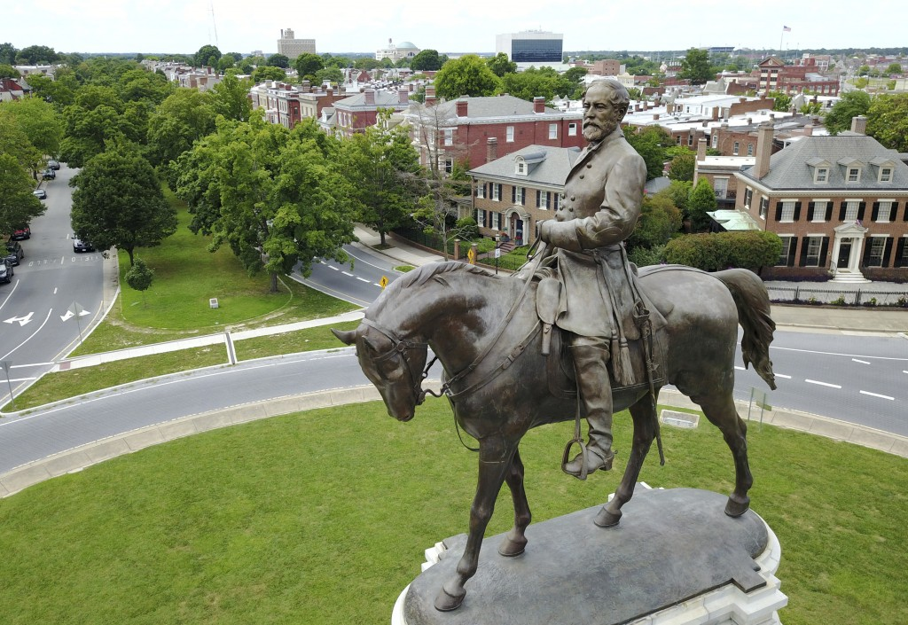 FILE - In this June 27, 2017 file photo a statue of Confederate Gen. Robert E. Lee stands in the middle of a traffic circle on Monument Avenue in Rich...